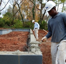 Masons Wriston McGee, left, and Terry Deese, of Monroe-based McGee Bros. masonry firm, work on the foundation of one of the eight new homes under construction in Grier Heights. Photo by Tony Brown