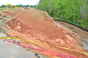 Under the watchful eyes of an engineer and town officials, work has begun to clean up the 130-foot sinkhole-turned-landslide in the Antiquity subdivision in Cornelius.   Photo by Tony Brown