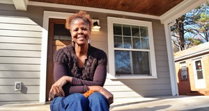 Donnetta Collier, project manager for Self-Help's revitalization efforts in Grier Heights, sits on the front porch of a house on Orange Street that the nonprofit developer rehabbed to the studs. It is for sale, but only to someone making less than 50 percent of the Charlotte area median income. Photo by Tony Brown