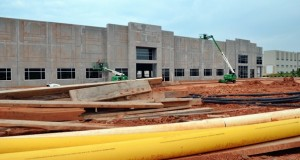 Construction workers install glazing and exterior finishes on the front of one new warehouse-office building at Steele Creek Commerce Park. Just behind it, earth-moving equipment clears the way for the slab foundation for another. Photo by Tony Brown