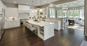 White cabinets, a large island with pendant lights, and contoured counter tops are increasingly popular choices among homebuyers. Photo courtesy of Toll Brothers