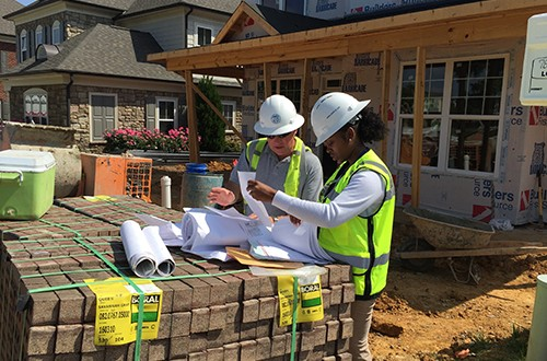 Outside the home, McKinney and Tilley, who is her mentor, check the construction plans as part of the inspection process. Knowing specific details is critical for inspectors to ensure a contractor meets mandated codes, Tilley says. Photo by David Dykes