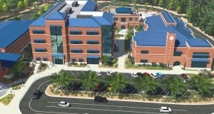 This artist rendering of the new academic center for Providence Day School shows where the new four-story classroom building (left, with glass front) will fit on campus, between the library and technology center. Drawing courtesy Providence Day School.